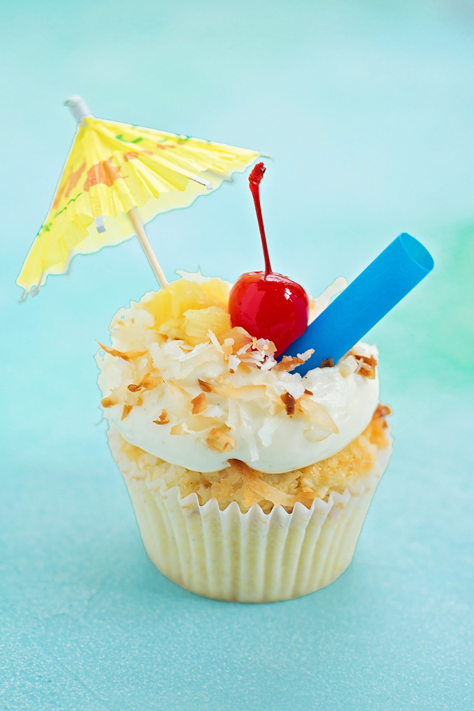 Piña colada cupcake recipe with a straw, umbrella, and cherry on top