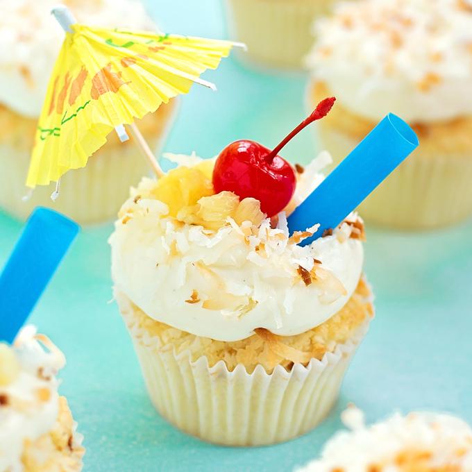 Piña Colada Cupcakes topped with an umbrella and a cherry