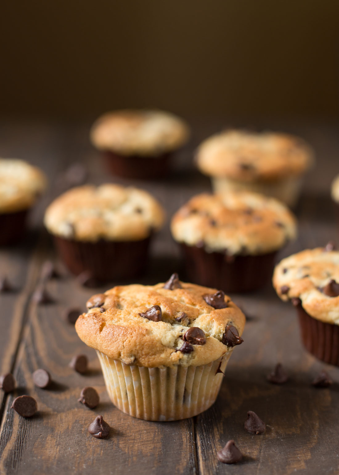 Bakery-style chocolate chip muffins on wood