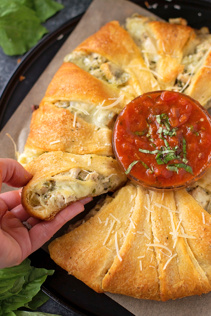 Pesto Chicken Crescent Ring with a bowl of marina in the middle for dipping