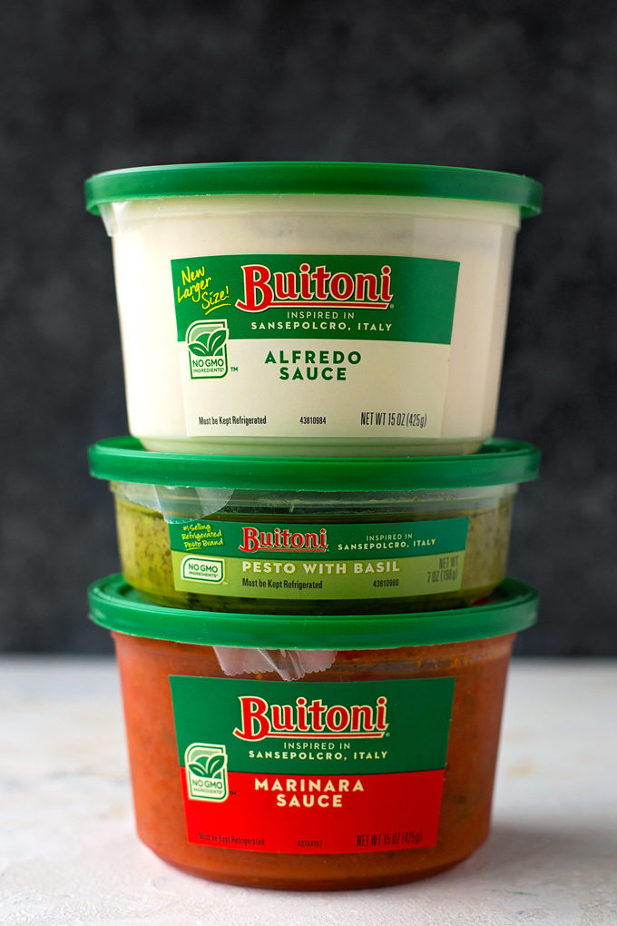 Containers of Buitoni Alfredo, Pesto, and Marinara stacked on top of each other