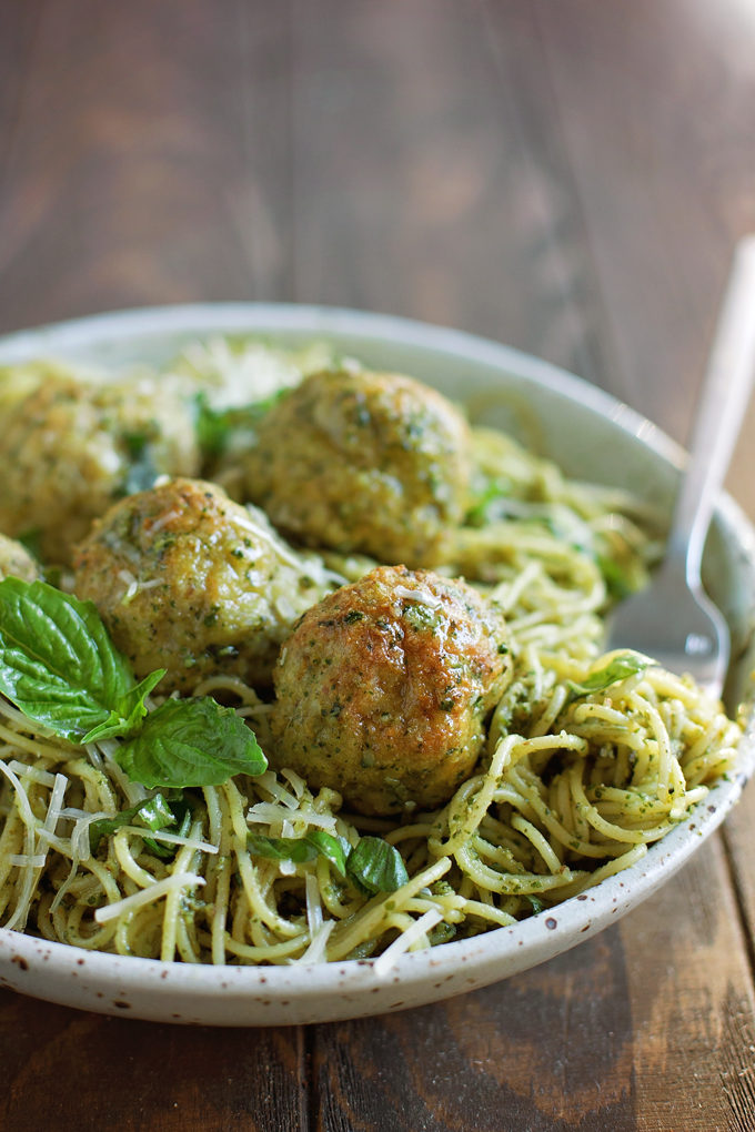 Pesto meatballs over noodles in bowl