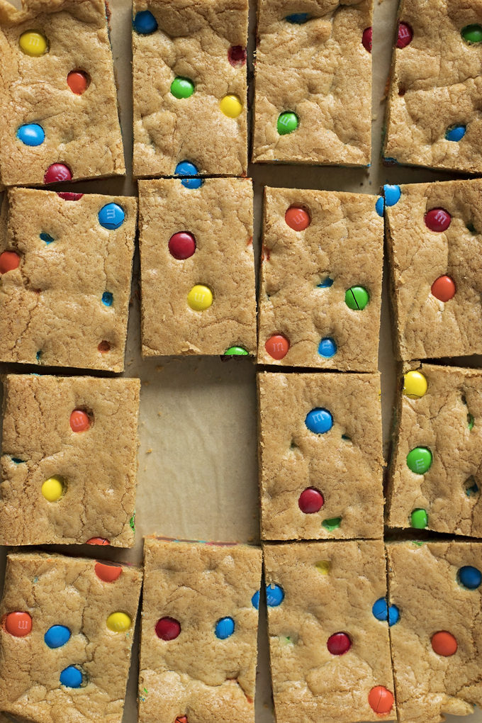 M&M cookie bars cut into squares with one missing. | lifemadesimplebakes.com