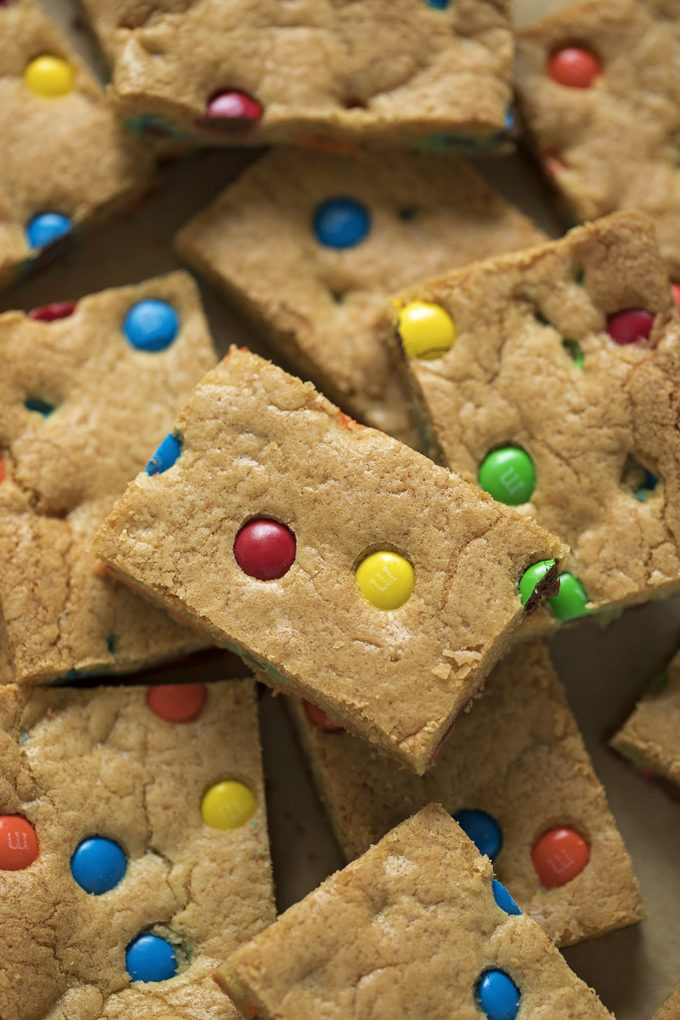 A pile of chewy M&M cookie bars. | lifemadesimplebakes.com