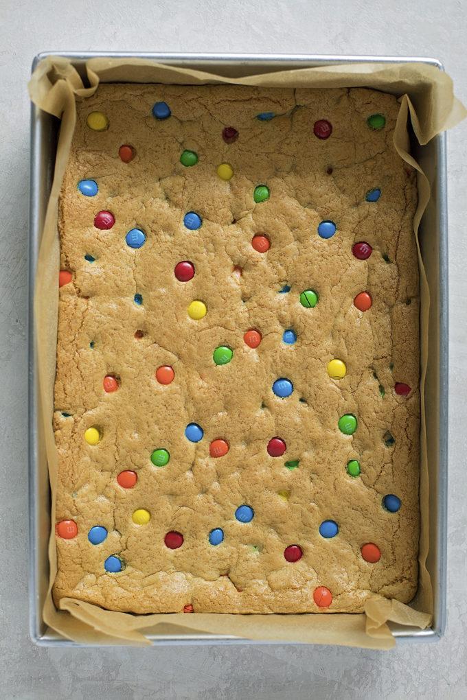 A pan of freshly baked M&M cookie bars. | lifemadesimplebakes.com