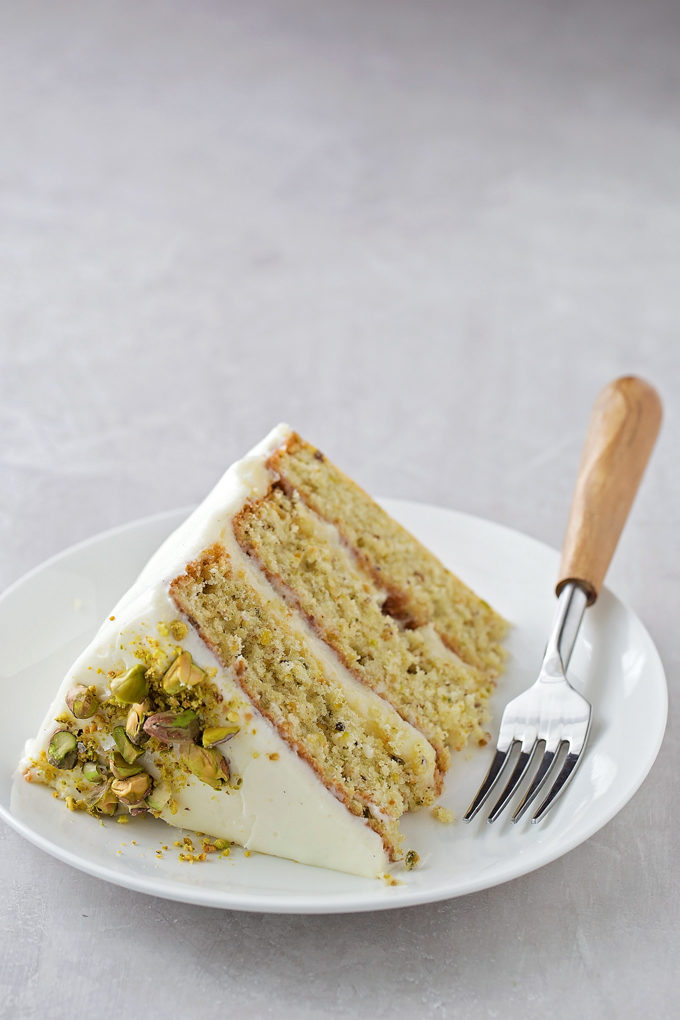 A slice of pistachio cake on a white plate with a fork
