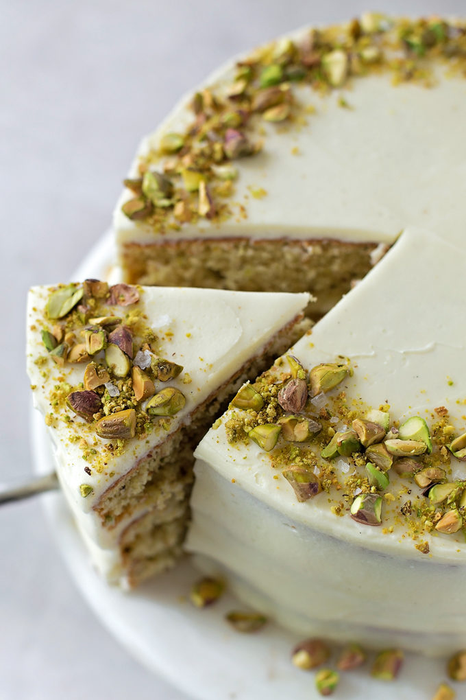 Taking a slice out of the pistachio layer cake with mascarpone frosting| lifemadesimplebakes.com