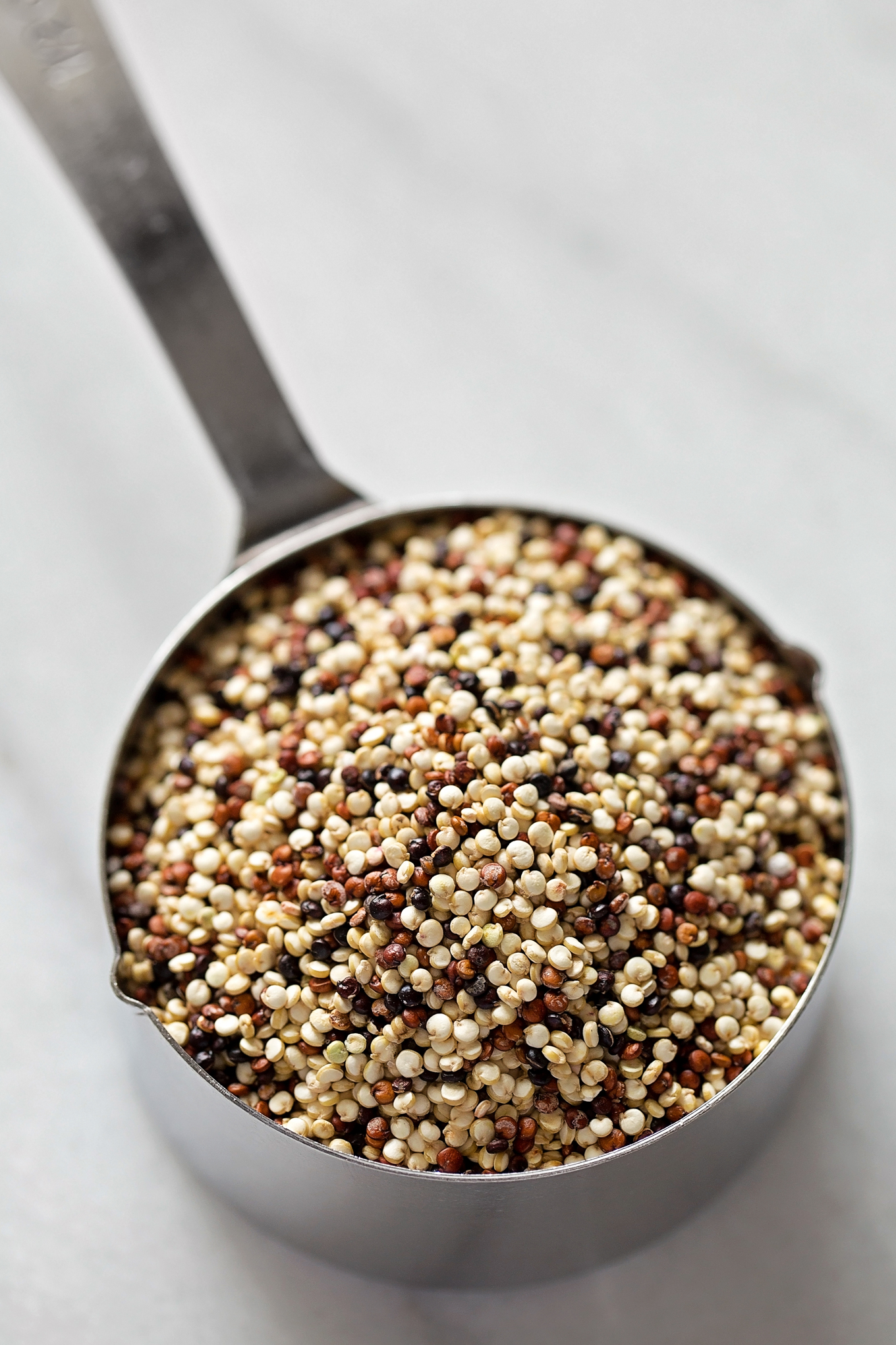 A measuring cup filled with tricolor quinoa for the southwestern quinoa salad. | lifemadesimplebakes.com