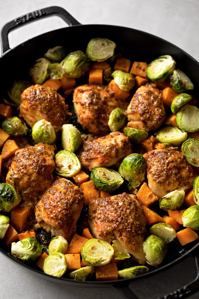 A cast iron skillet with maple dijon roasted chicken and vegetables. | lifemadesimplebakes.com