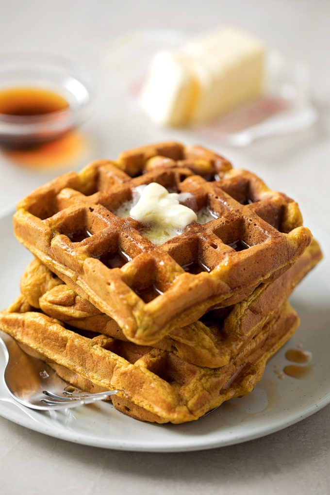 A stack of crispy pumpkin waffles topped with butter.