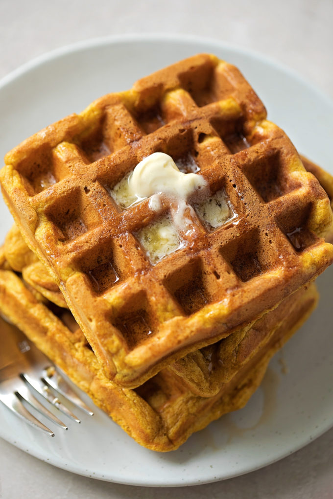 Pumpkin waffles piled high with a drizzle of maple syrup and a pat of butter.