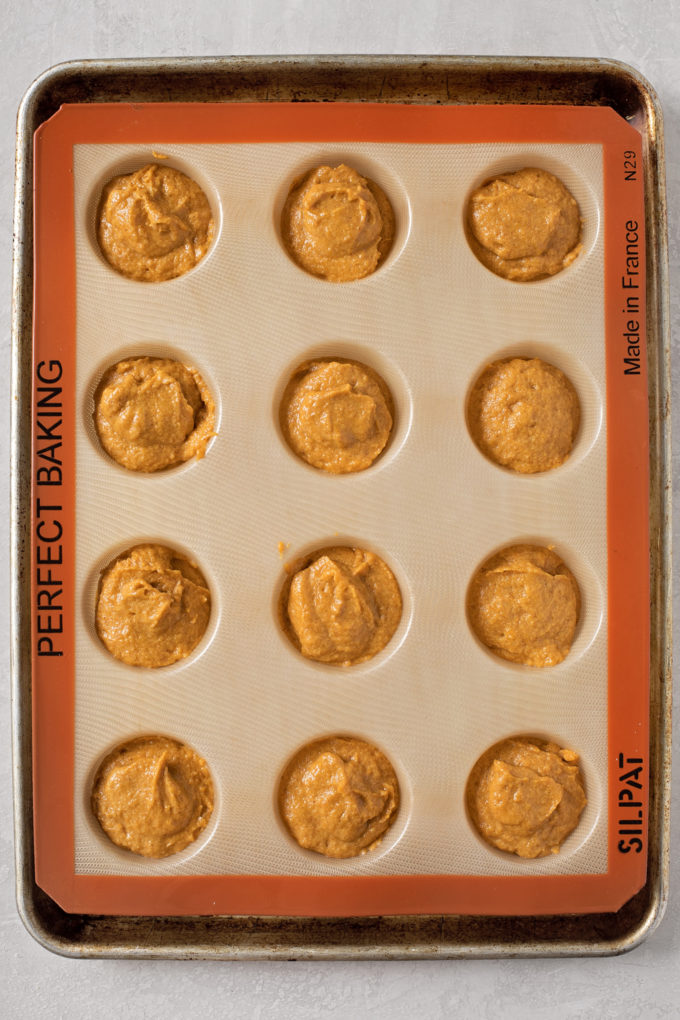 A silicone mold filled with batter ready to be baked into whole wheat pumpkin muffins. | lifemadesimplebakes.com