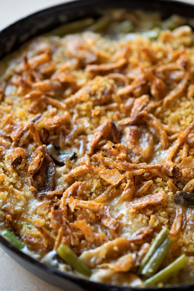 A skillet of creamy green bean casserole topped with fried onions and panko.