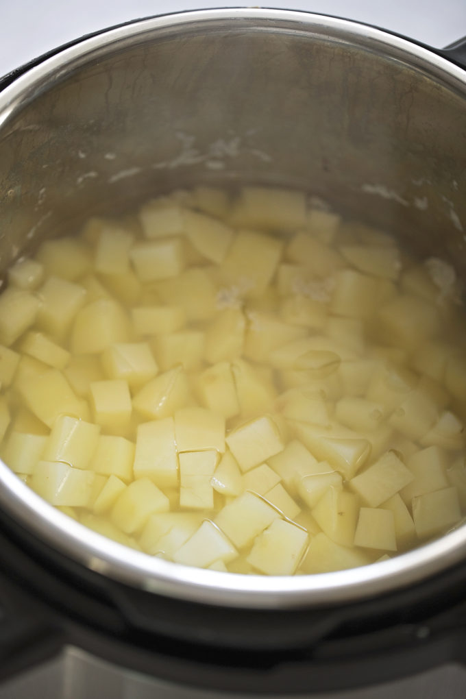 Cubed potatoes sitting in water inside of the Instant Pot.