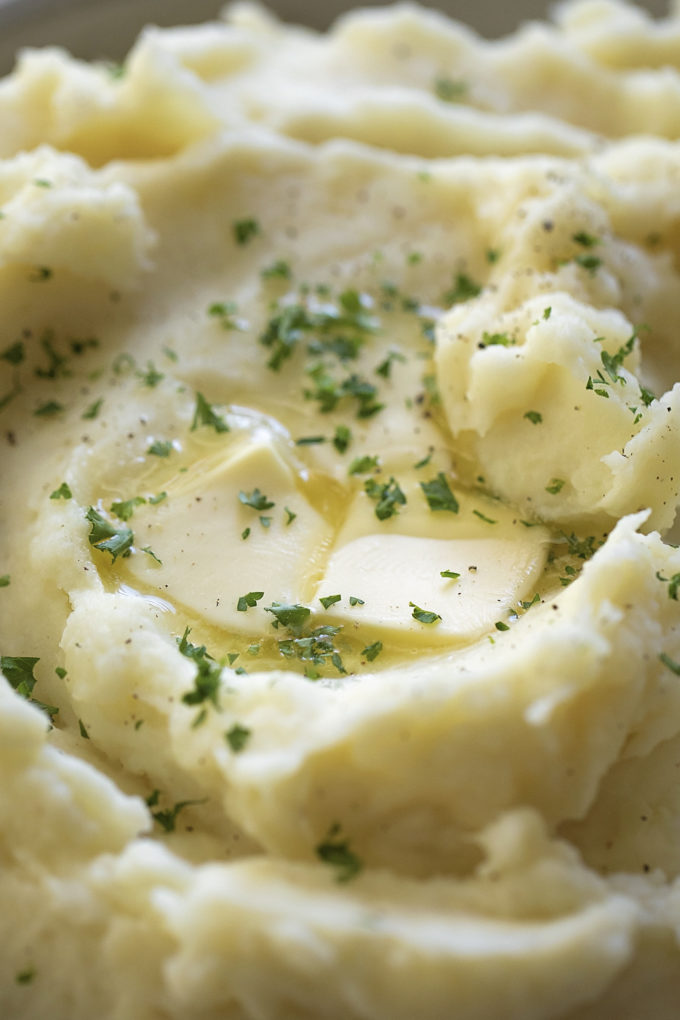 A close up shot of Instant Pot mashed potatoes garnished with parsley and butter.