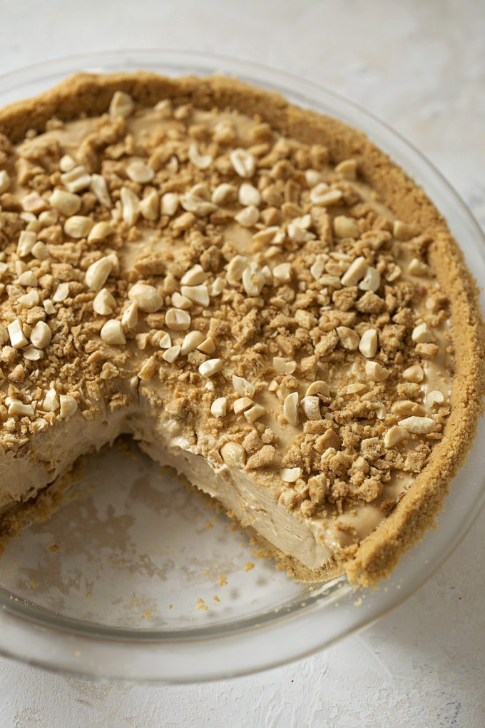 An overhead view of creamy no-bake peanut butter pie with a slice missing.