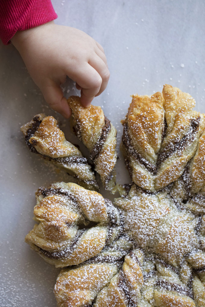 A small hand pulling a piece off of a Nutella puff pastry snowflake.