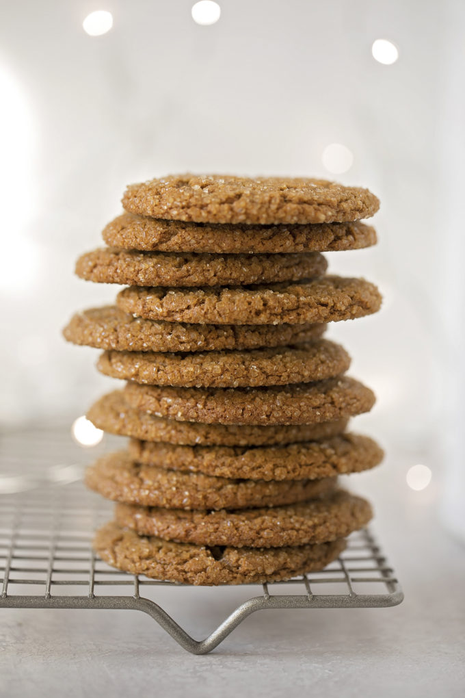 A stack of sparkling ginger molasses cookies on a cooling rack.