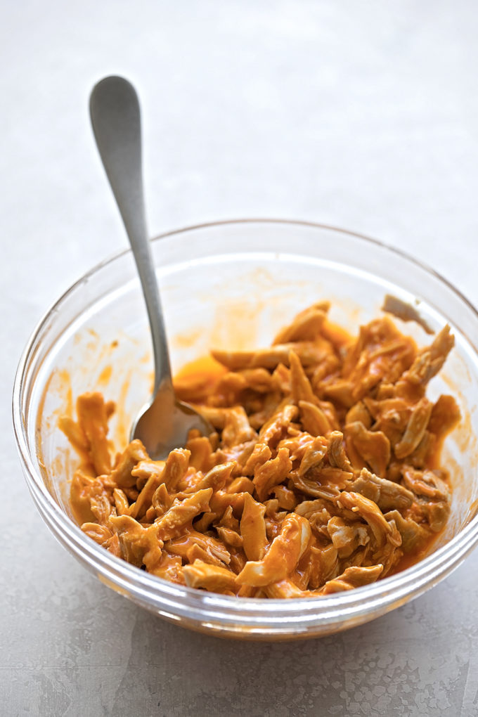 A bowl of shredded chicken thighs tossed in buffalo chicken sauce for the buffalo chicken stuffed shells.