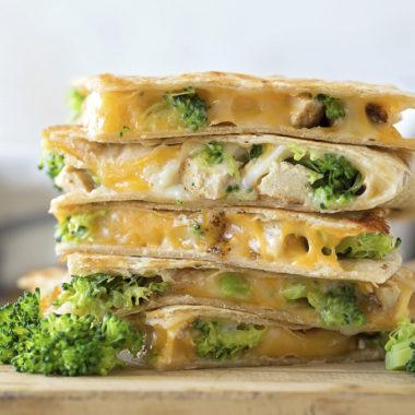 A stack of cut chicken broccoli quesadillas fresh off the heat.