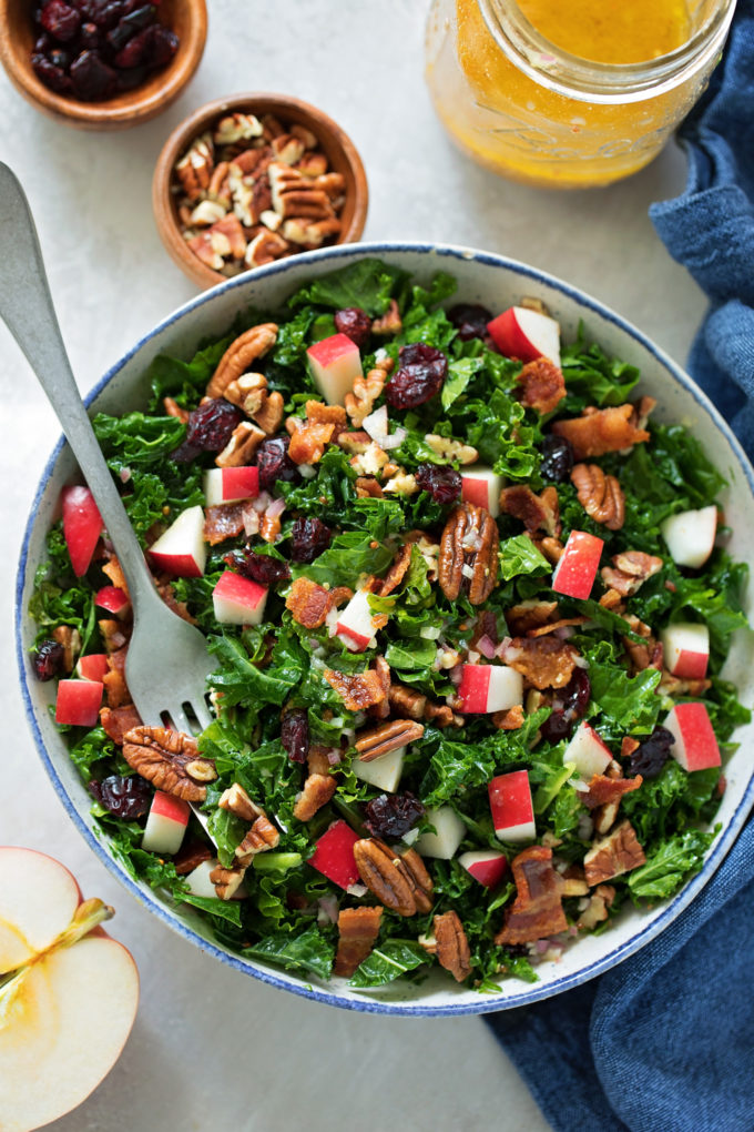 An overhead view of a big serving bowl of cranberry apple pecan kale salad with dress ing and extra toppings.