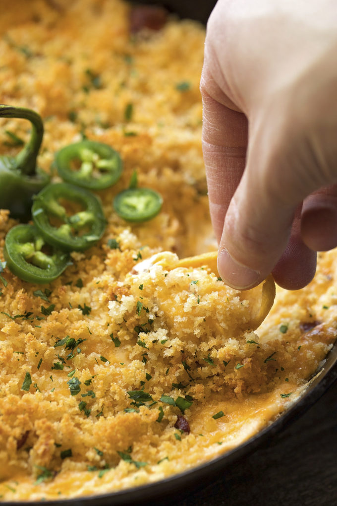 Scooping up a chip full of baked jalapeño popper dip.