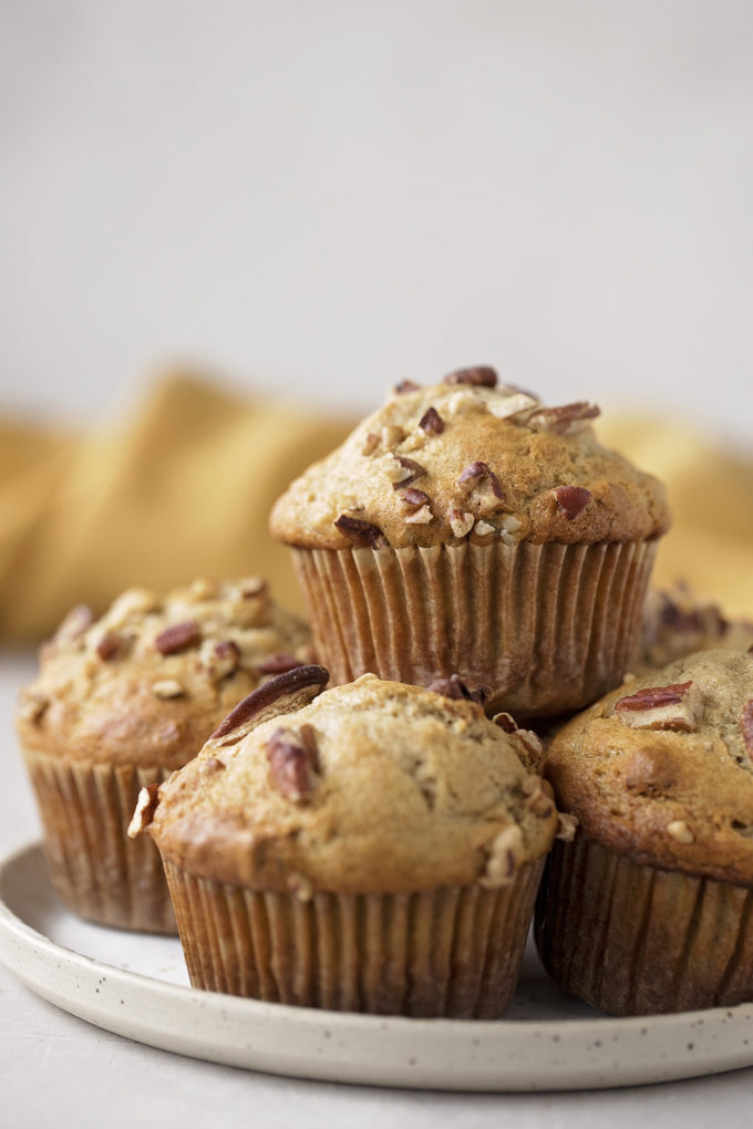 A plate full of sky-high banana nut muffins.