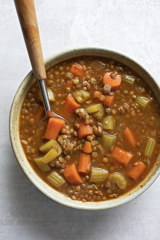 An overhead view of a bowl of easy vegetable lentil soup with a spoon.