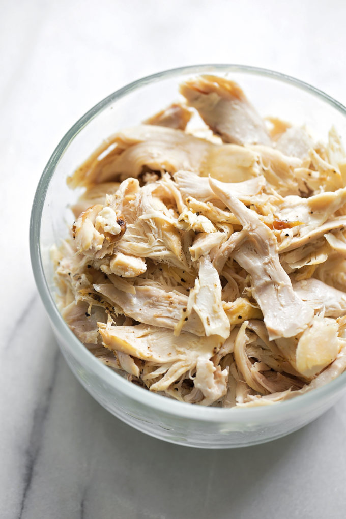 A bowl of pulled rotisserie chicken for the filling of chicken tortilla casserole.