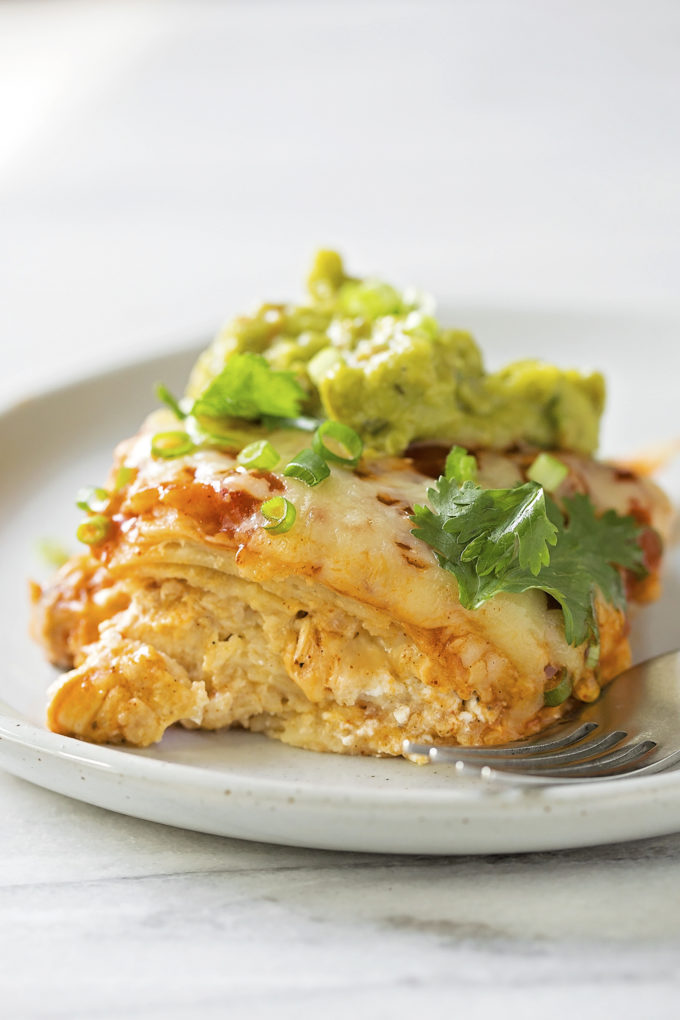 A plate with a serving of chicken tortilla casserole topped with homemade guacamole.