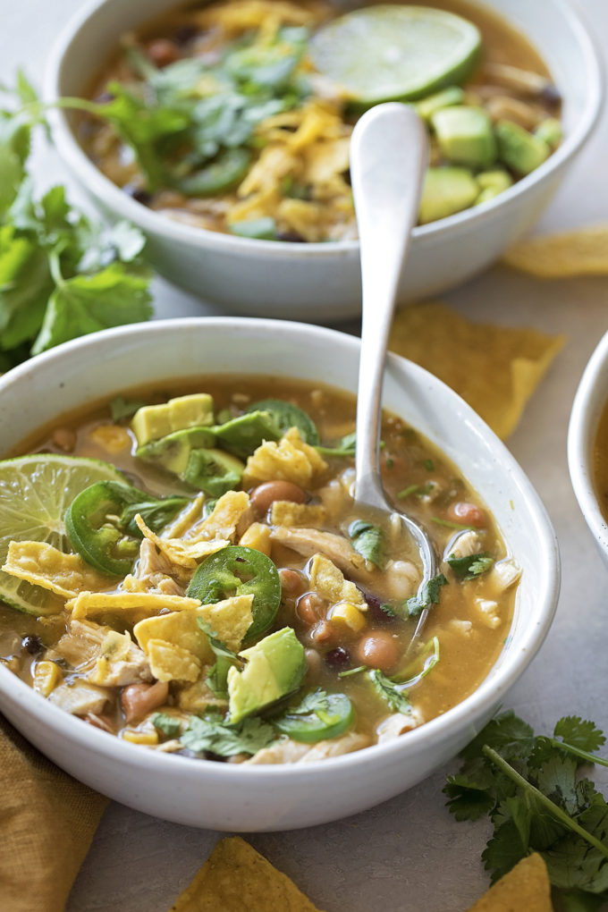 A close up of jalapeño lime chicken chili garnished with avocado and tortilla chips.