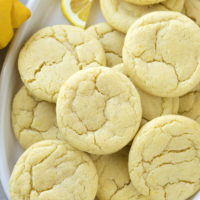 A plate piled with freshly baked lemon sugar cookies.