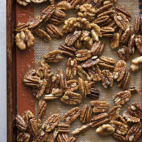 A lined baking sheet with perfect candied nuts scattered about.
