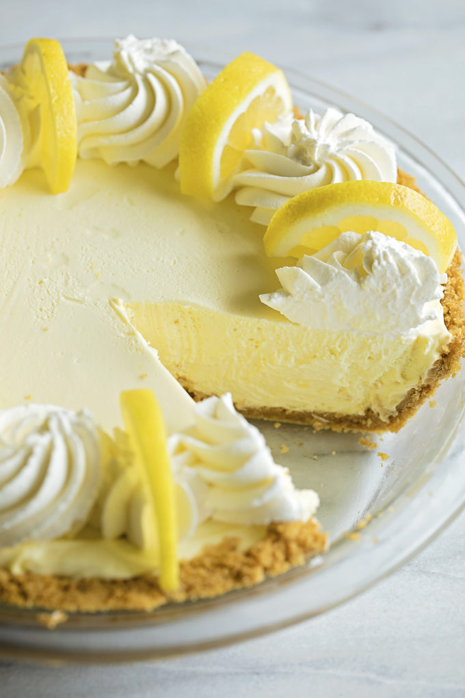 A close up shot of heavenly lemon cream pie with a slice missing.