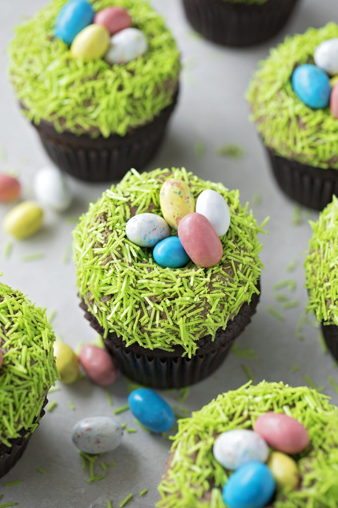 An arrangement of cute Easter cupcakes topped with faux easter grass and eggs.