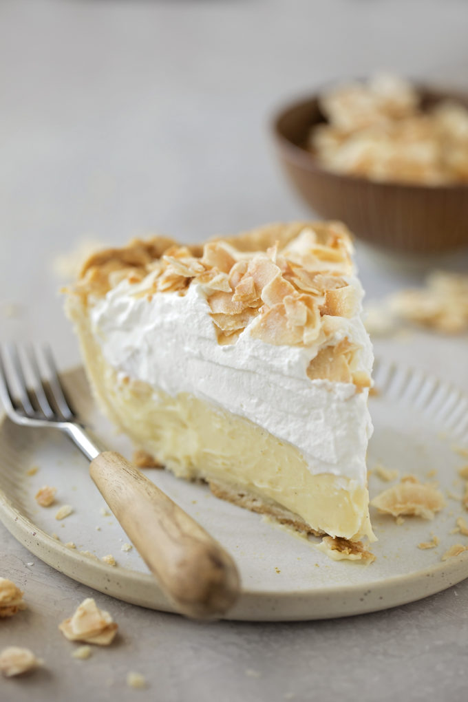 A slice of perfect coconut cream pie topped with whipped cream and toasted coconut.