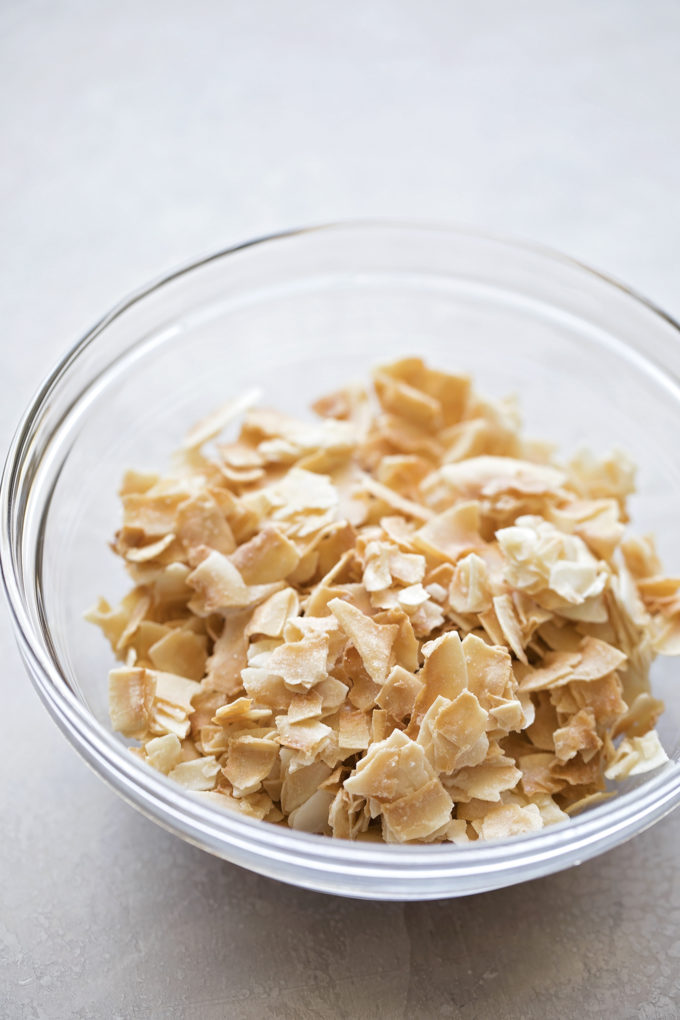 A bowl of toasted coconut for the filling and topping of homemade coconut cream pie.