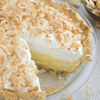 A close up of the perfect coconut cream pie with a slice missing.