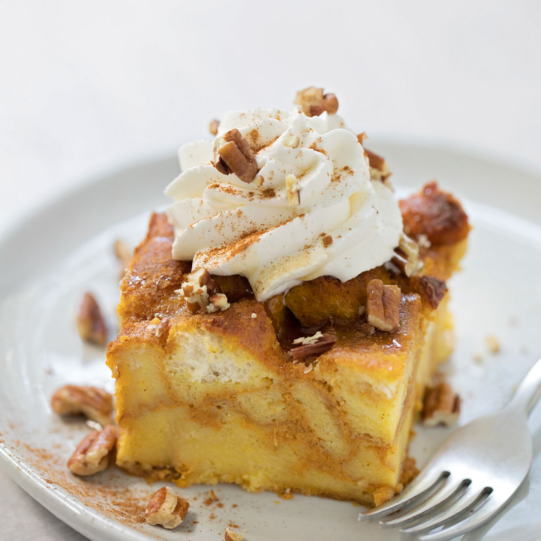 Pumpkin bread pudding slice with whipped cream and pecans on plate