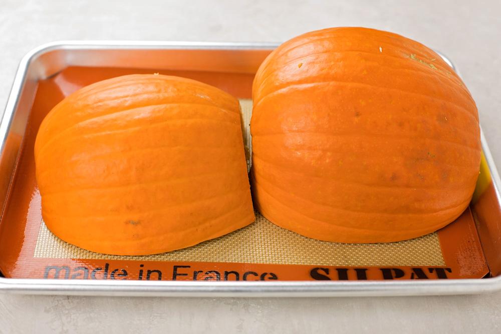 Sugar pumpkin cut in half on baking sheet