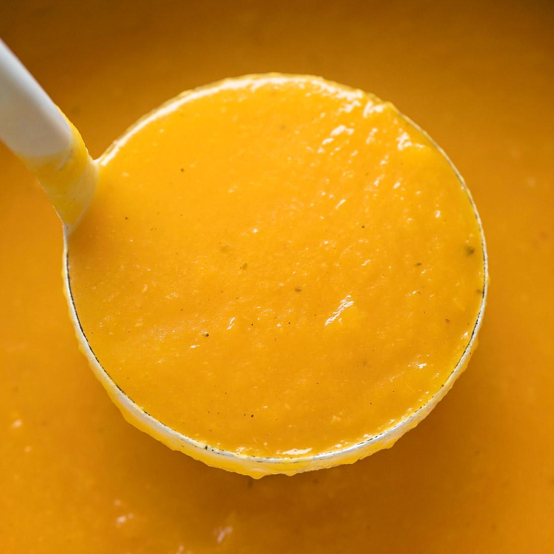 Ladle full of creamy pumpkin soup
