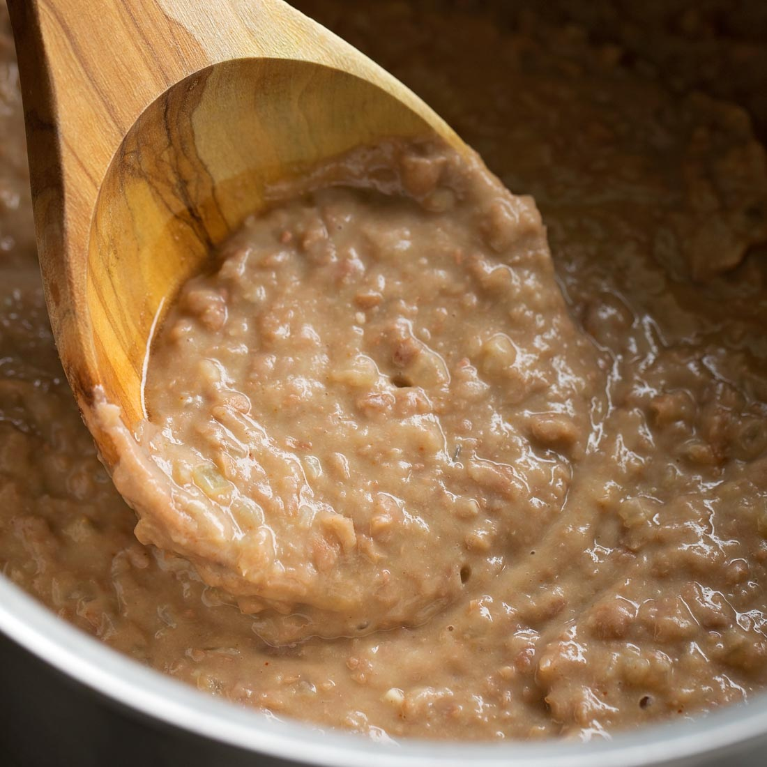 Creamy refried pinto beans on wooden spoon in pot