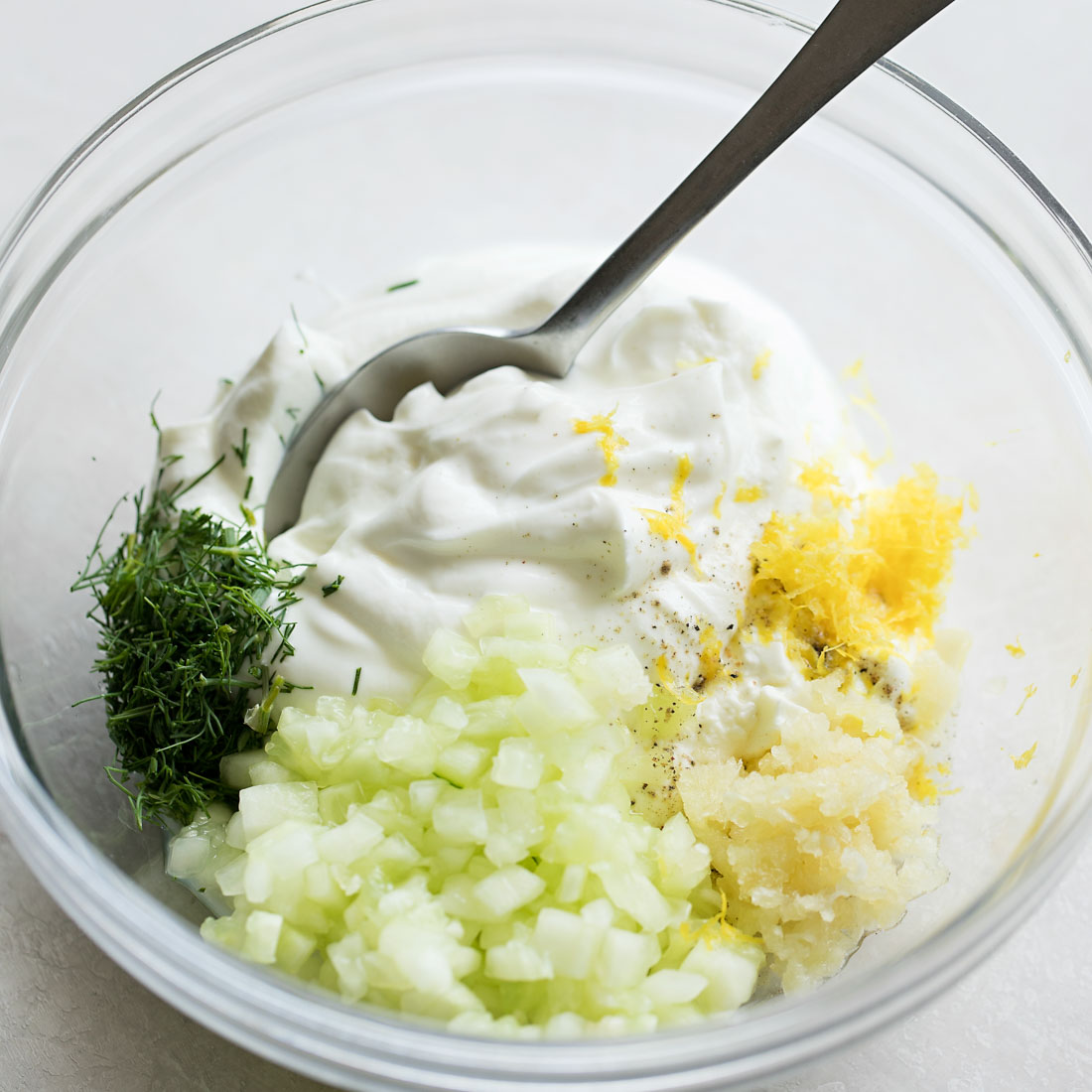 Tzatziki ingredients in glass bowl