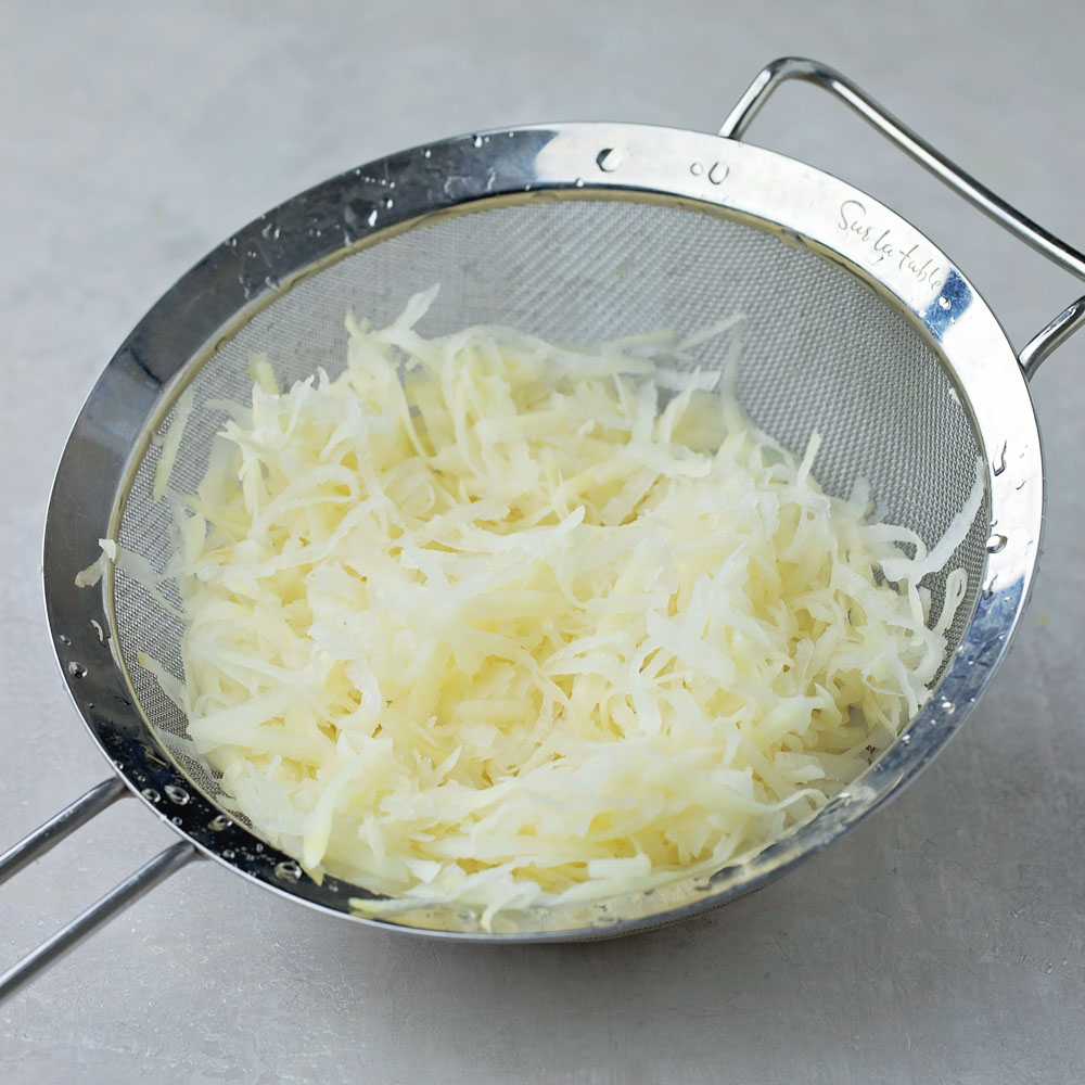 Shredded potatoes in colander for hash browns