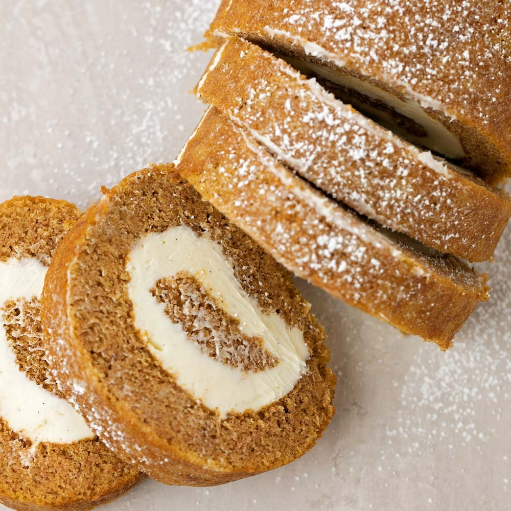 Classic pumpkin roll sliced and sprinkled with powdered sugar