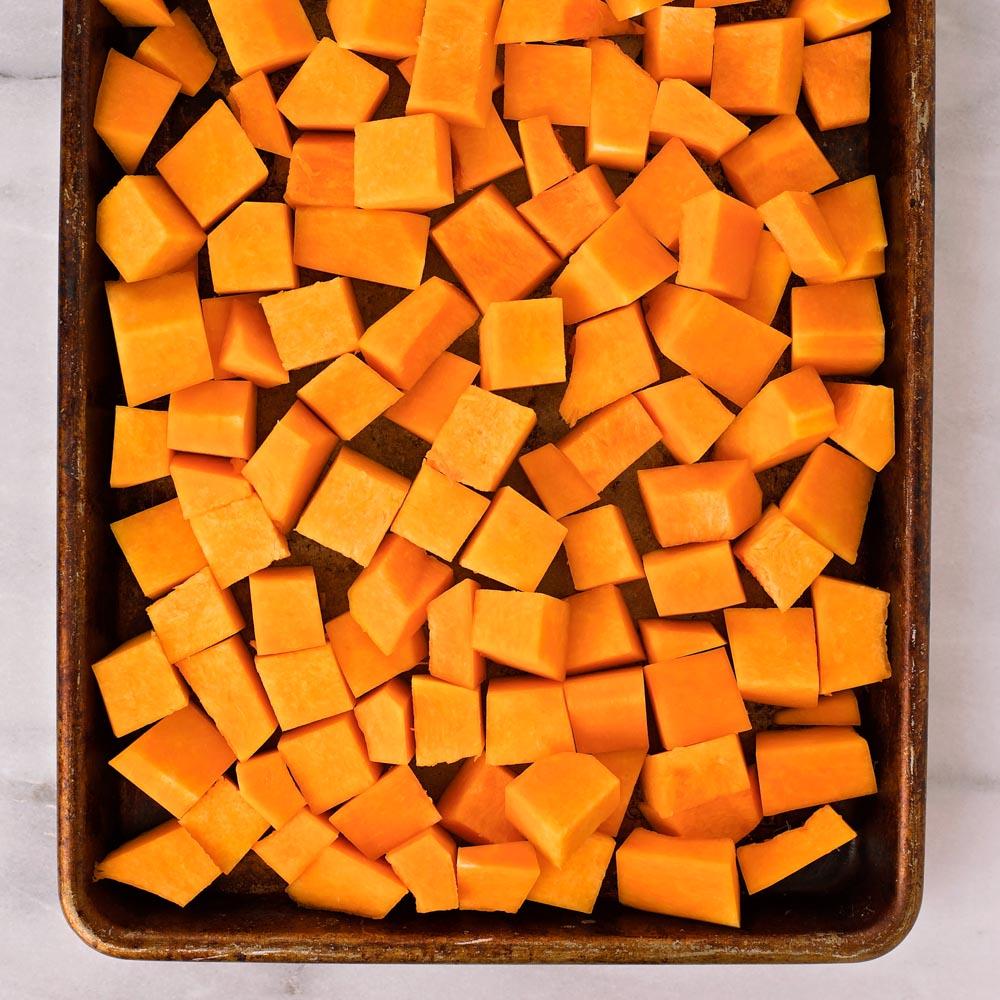 Butternut squash cubes on baking sheet