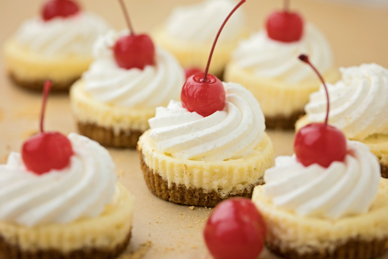 Mini cheesecakes with whipped cream and cherries