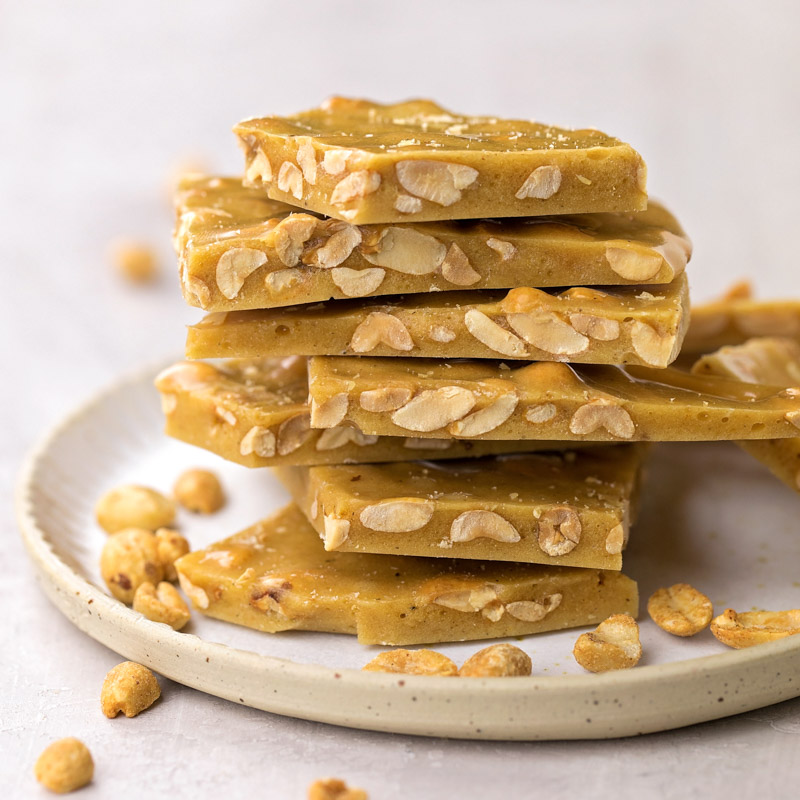 Homemade peanut brittle stacked on plate