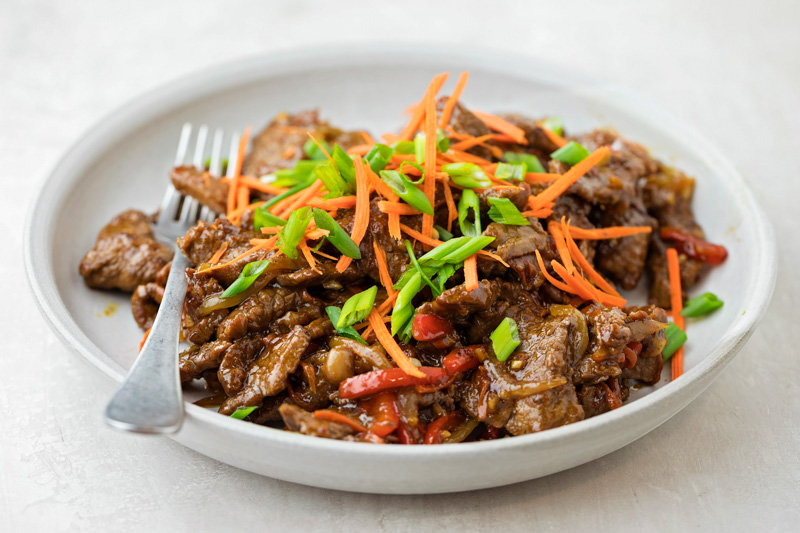 Szechuan beef with toppings on plate