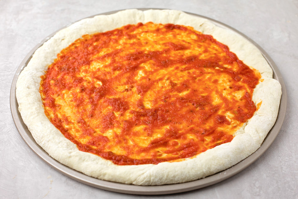 Homemade pizza sauce spread out onto pizza dough
